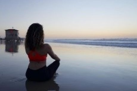 person meditating on the beach
